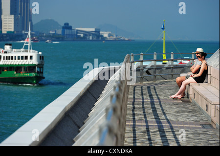 A western couple sitting near the Star Ferry terminal, Hong Kong SAR - Stock Image