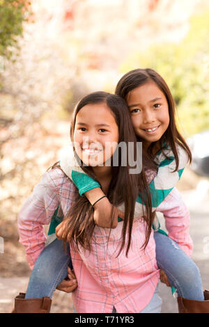 Portrait of two happy sisters smiling. - Stock Image