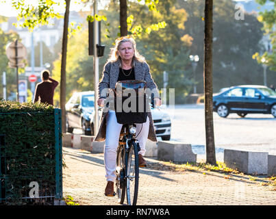 Strasbourg, Alsace, France, mature woman biking on pavement, - Stock Image