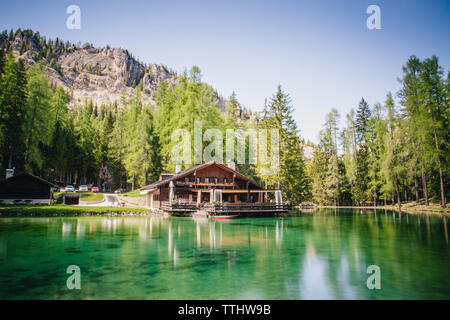 View of the lodge over the turquoise waters of Lago Ghedina, an alpine lake in Cortina D'Ampezzo, Dolomites, Italy - Stock Image