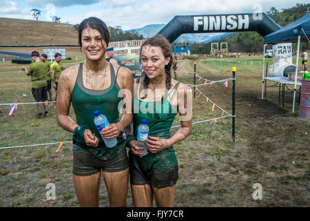 Two young women athletes at the finish line after competing in an 8km obstacle course - Stock Image