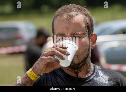 At the end of a mud run a competitor drinks from a polystyrene cup - Stock Image