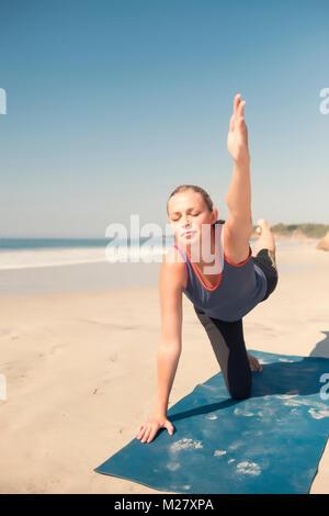 Caucasian woman exercising yoga at a beach, eyes closed. - Stock Image