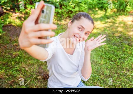 Young funny girl take selfie from hands with phone sitting on green grass park or garden background. Portrait of young attractive woman making selfie - Stock Image