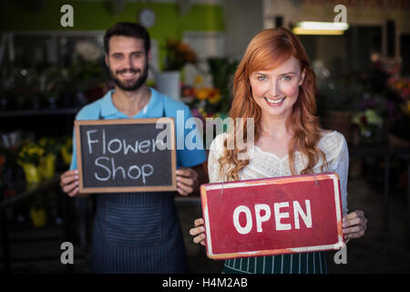 Woman holding open signboard and man holding slate with flower shop sign - Stock Image