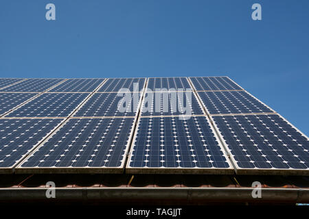 solar panel soak up the blue sky sun, modern solar cells or photovoltaic on the roof of an old woodshed with new gutter in front of azure sky - Stock Image
