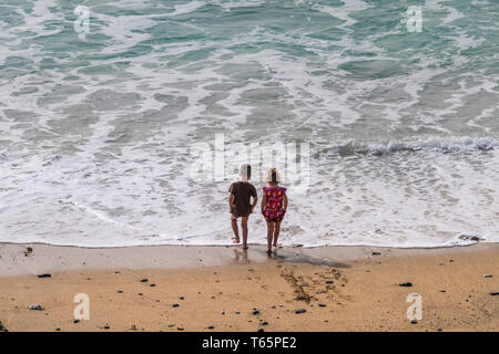 Two young children paddling in the sea at Fistral Beach in Newquay in Cornwall. - Stock Image