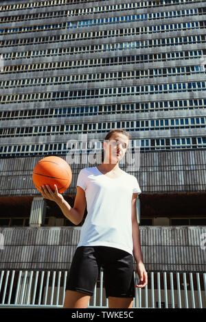 Portrait of a young female basketball player holding the ball against a heavy urban building - Stock Image