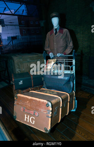 A Hogwarts Railway Porter pushes a trolley containing the luggage of Hermione Granger along platform 9 3/4 at Kings Cross, Warner Brothers Studio Tour - Stock Image
