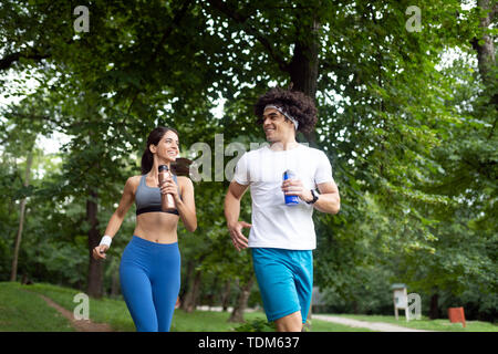 Couple jogging and running outdoors in nature - Stock Image