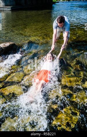 Father playing with his daughter in a river. - Stock Image