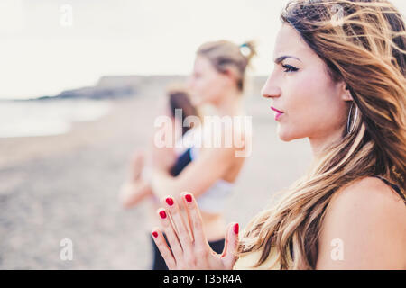 Portrait of cute blonde girl in yoga active meditation position with friends near her - people in healthy lifestyle outdoor at the beach - defocused b - Stock Image
