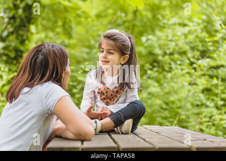 Young mom and her little girl have fun together on wooden bench in forest.Happy mother and daughter moments with love and natural emotion - Stock Image