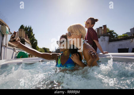 Young women friends taking selfie in sunny rooftop hot tub - Stock Image