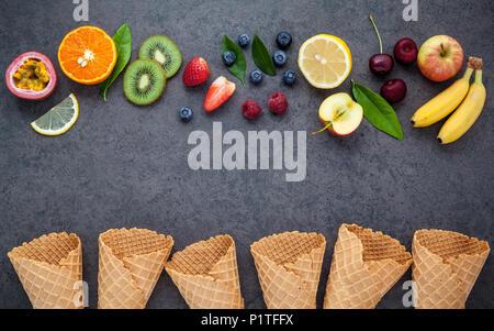 Flat lay various fresh fruits raspberry ,blueberry ,strawberry ,orange ,banana ,passion fruit ,apple and cherry setup on dark stone background . Summe - Stock Image