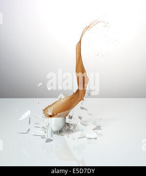 A dropped cup of tea smashing on impact - Stock Image