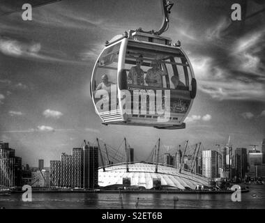 An Emirates Air Line Cable Car passes over the River Thames and the O2 Arena in London, England. Is it futuristic or just a normal way to travel to work? Photo © COLIN HOSKINS. - Stock Image