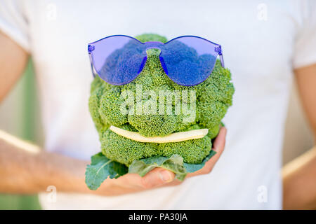 Holding broccoli with sunglasses and bean in form of the head on the white t-shirt background, healthy food concept - Stock Image