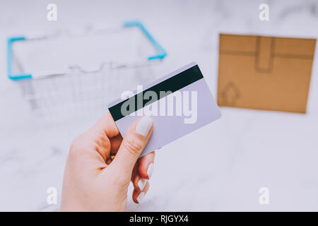 woman's hand holding payment card with mini cardboard delivery icon and shopping basket in the background, concept of ordering and receiving your purc - Stock Image