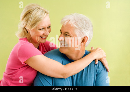 Portrait of smiling middle aged couple in front of green wall hugging - Stock Image