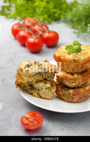 healthy breakfast. broccoli cheese bites (muffins), fresh tomatoes, fresh herbs on a gray concrete background - Stock Image