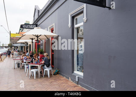 People eating under umbrellas on the footpath outside Pilgrims Vegetarian Cafe in Milton on the New South Wales south coast, Australia - Stock Image