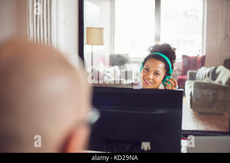 Woman wearing headphones talking to bald man and smiling - Stock Image
