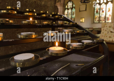 Votive candles lit as prayers for loved ones inside a Christian church - Stock Image