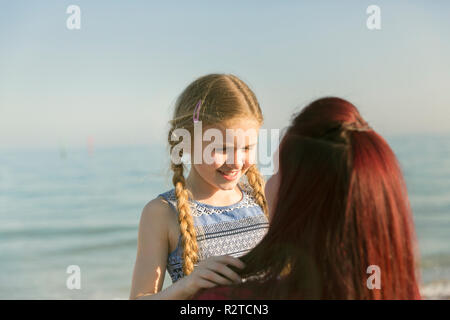 Affectionate mother holding daughter on sunny ocean beach - Stock Image
