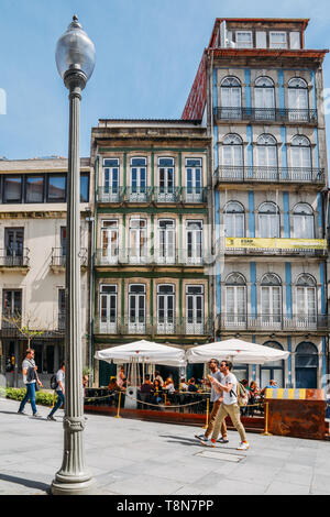 Porto, Portugal - April 29, 2019: Tourists walking next to narrow colourful buildings with cafes in the historic centre of Porto - UNESCO - Stock Image