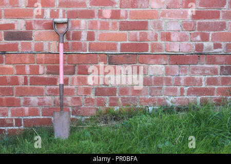 Spade standing on grass, leaning against a brick wall, in a garden. - Stock Image