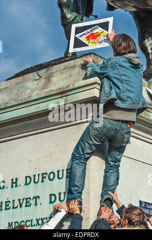 Geneva, Switzerland. 8th January 2015. A journalist climbing up on a statue of Swiss hero General Dufour to place - Stock Image