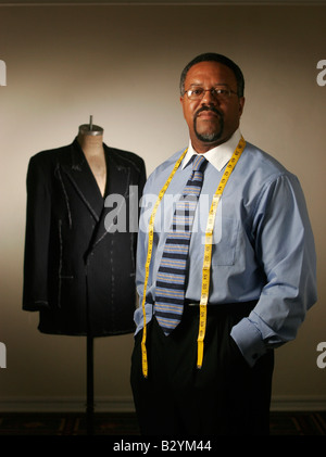 A professional tailor pictured with a tailor's dummy in his workshop. - Stock Image