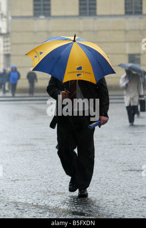 A man shelters from a downpour under a Standard Life umbrella, Edinburgh - Stock Image