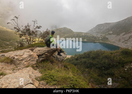 A man hiker hiking mountain with a backpack trails outdoors lifestyle landscape scenery backpacking rucksack - Stock Image