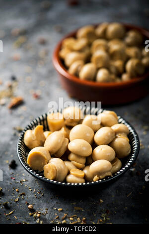 closeup of some bowls with cooked mini common mushrooms placed on a stone surface, sprinkled with different spices - Stock Image