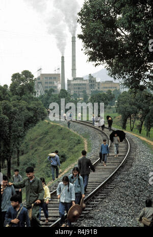 China 1973 factory workers leaving factory using the train track as a path - Stock Image