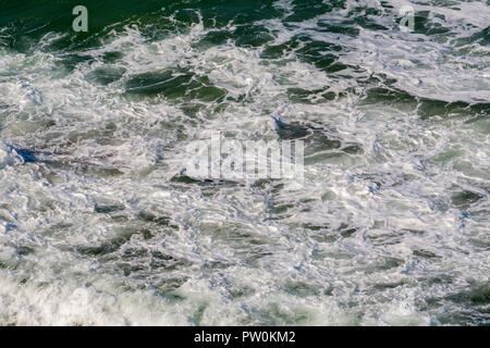 High angle shot of waves breaking and dissipating. - Stock Image