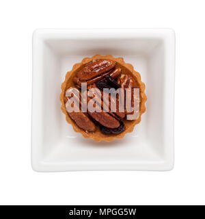 Walnut tart in a square bowl isolated on white background - Stock Image
