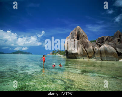 Couple in aqua waters near granite rocks at Anse Source d' Argent on La Digue Island in Seychelles - Stock Image