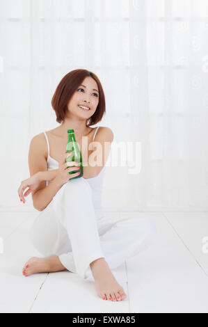 Young woman sitting on the floor and holding a carefe with smile, - Stock Image