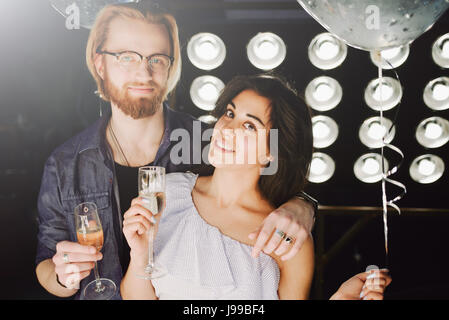 Young couple celebrates their love toasting with champagne glass with a hollywood style backlight, flare  used to - Stock Image