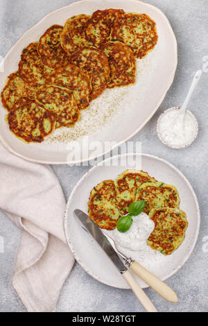 Fritters of zucchini with fresh parsley and Basil. Delicatessen vegetable pancakes with sauce from sour cream and dill. Selective focus - Stock Image