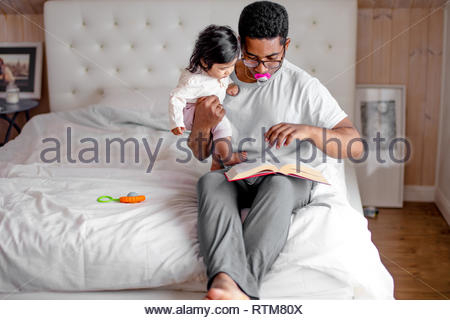 funnt dad with a dummy in his mouth showing pictures to his little child, close up photo, entertainmnet - Stock Image
