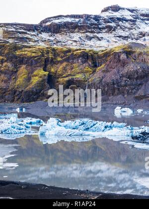 Chunks of ice from the end of a glacier floating in a glacial lagoon in southern Iceland - Stock Image