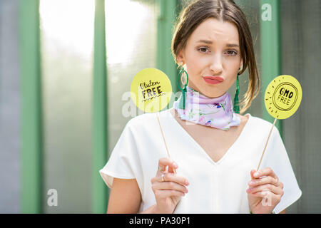 Beautiful woman holding green plates with healthy eating slogans outdoors on the green background - Stock Image