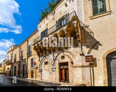 A medieval street in the Old Town features the Balsamo Loggia, a 14th century intricately carved balcony, in Brindisi, Italy located near Piazza Duomo - Stock Image