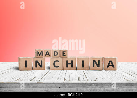 Made in China sign on a wooden desk with a red wall in the background - Stock Image