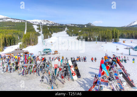 LAKE LOUISE, CANADA - MAR 23, 2019: Skis and snowboards on racks at Lake Louise in the Canadian Rockies near Banff with ski slopes and chair lifts in  - Stock Image