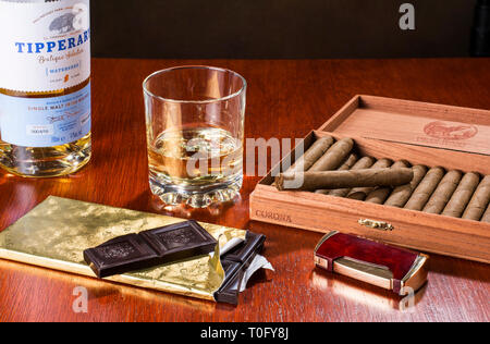 Dark chocolate, whisky and cigars go very well together, especially after dinner - Stock Image